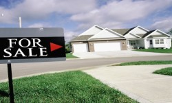 House on suburban street with 'For Sale' sign in foreground --- Image by © Royalty-Free/Corbis